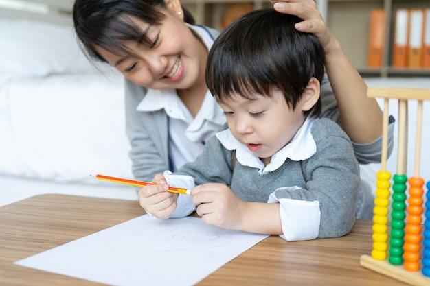 Die junge mutter, die ihren sohn unterrichtet, schreiben auf papier mit liebe