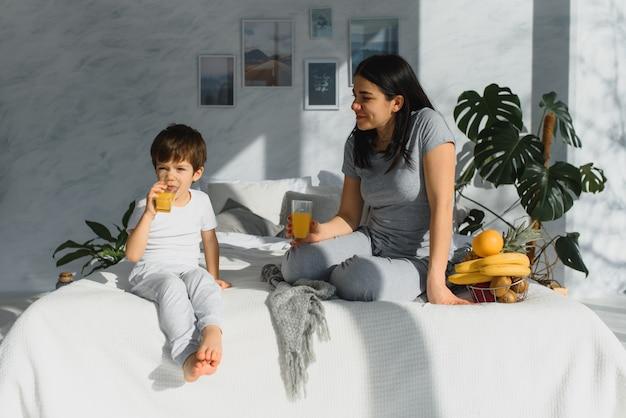 Die junge mutter mit ihrem 4 jahre alten kleinen sohn im pyjama entspannt sich und spielt im bett