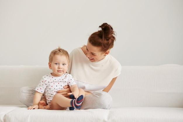 Die junge mutter mit ihrem einjährigen kleinen sohn im pyjama entspannt sich