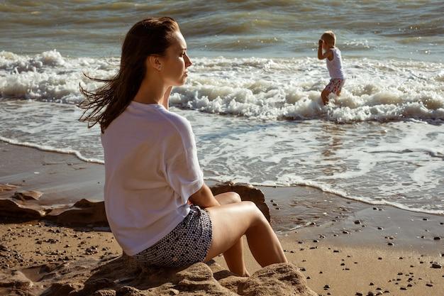 Die junge mutter sieht ihrem sohn zu, wie er an einem sonnigen sommertag am meer spielt