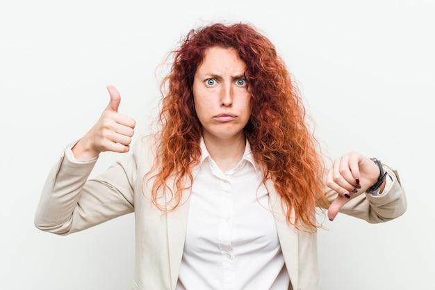 Die junge natürliche rothaarigegeschäftsfrau, die gegen das weiß sich zeigt daumen und daumen unten, schwierig lokalisiert wird, wählen
