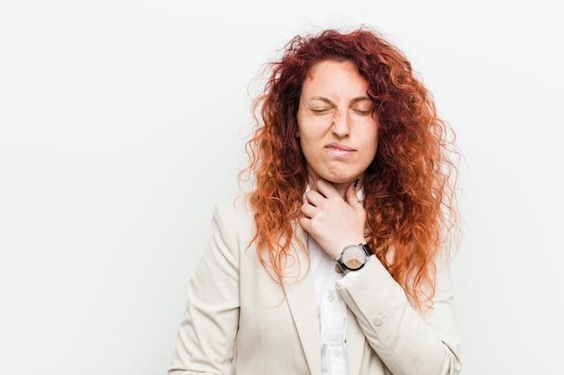 Die junge natürliche rothaarigegeschäftsfrau, die gegen weiß lokalisiert wird, leidet die schmerz in der kehle wegen eines virus oder einer infektion.