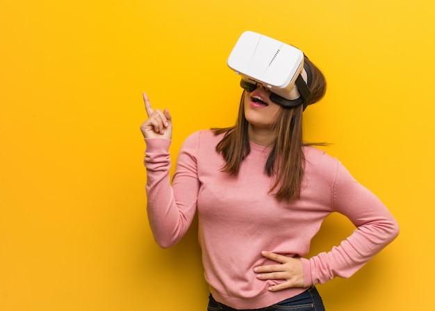 Die junge nette frau, die eine virtuelle realität trägt, googelt das zeigen auf die seite mit dem finger