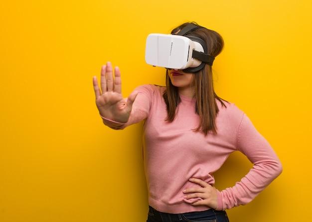 Die junge nette frau, die eine virtuelle realität trägt, googelt, hand in front setzend