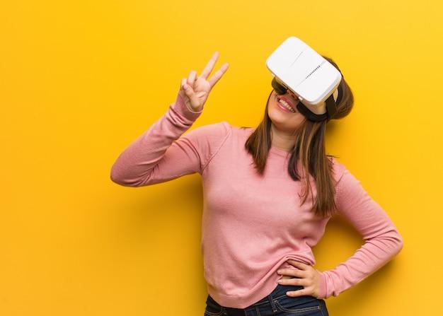 Die junge nette frau, die eine virtuelle realität trägt, googelt, nummer zwei zeigend