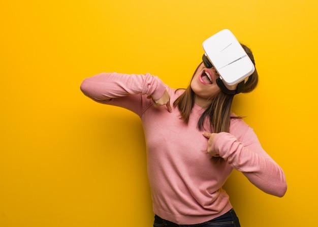 Die junge nette frau, die eine virtuelle realität trägt, googelt überrascht, fühlt sich erfolgreich und wohlhabend