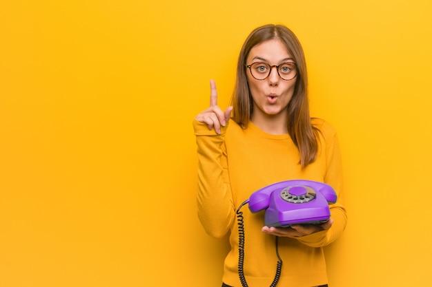 Die junge recht kaukasische frau, die eine großartige idee hat, hält ein weinlesetelefon.