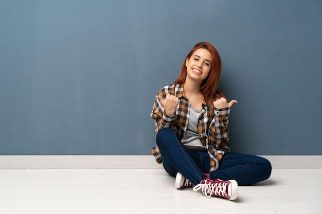 Die junge rothaarigefrau, die auf dem bodengeben daumen sitzt, up geste und das lächeln