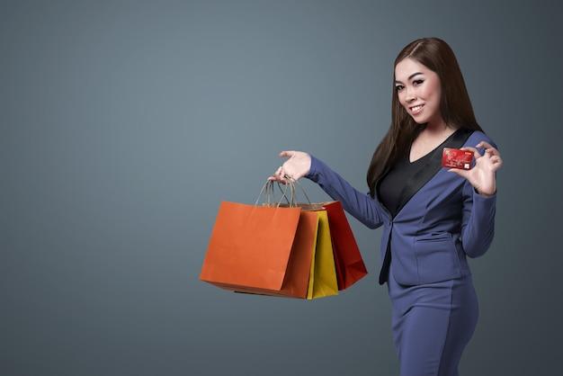 Die junge schöne asiatische frau, die einkaufstaschen hält und zeigen ihre kreditkarte