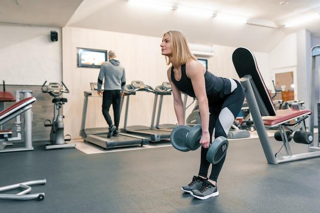 Die junge schöne blonde frau, die stärke tut, trainiert mit dummköpfen in der turnhalle