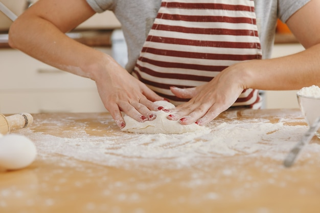 Die junge schöne glückliche frau, die an einem tisch mit mehl sitzt, teig knetet und in der küche einen kuchen zubereitet. kochen nach hause. essen aus nächster nähe zubereiten.