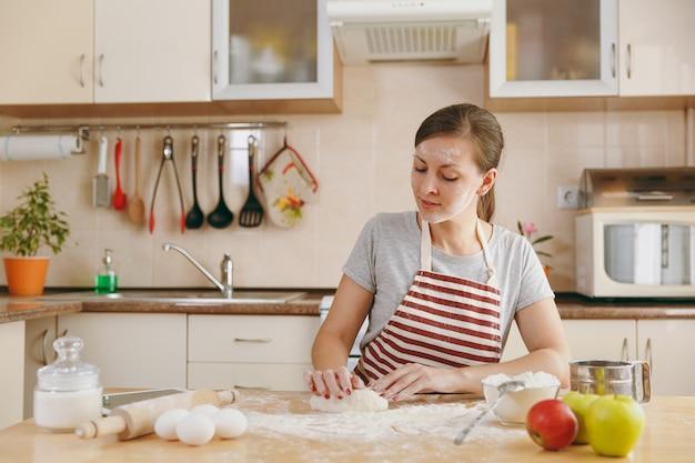 Die junge schöne glückliche frau, die an einem tisch mit mehl sitzt, teig knetet und in der küche einen kuchen zubereitet. kochen nach hause. essen zubereiten.