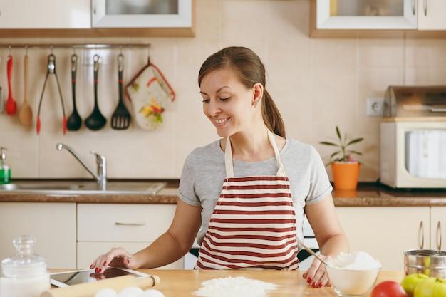 Die junge schöne glückliche frau, die nach einem rezept für kuchen in tablette in der küche sucht. kochen nach hause. essen zubereiten.