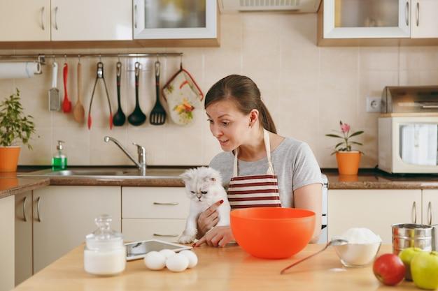 Die junge schöne glückliche frau mit einer weißen perserkatze, die nach einem rezept für kuchen in einer tablette in der küche sucht. kochen nach hause. essen zubereiten.
