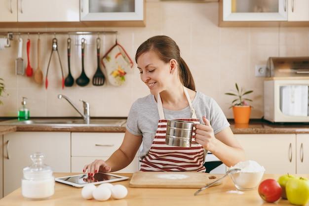Die junge schöne glückliche frau siebt mehl mit einem sieb und sucht in der küche nach einem rezept für kuchen in tablette. kochen nach hause. essen zubereiten.