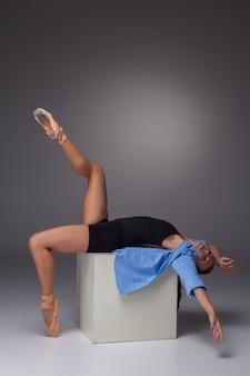 Die junge schöne moderne arttänzerin, die auf weißem würfel auf einem grauen hintergrund des studios aufwirft