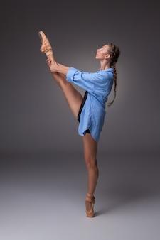 Die junge schöne moderne arttänzerin in einem blauen hemd, das auf einem grauen hintergrund des studios aufwirft