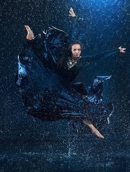 Die junge schöne moderne tänzerin, die unter wassertropfen tanzt