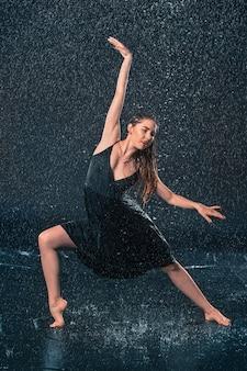 Die junge schöne moderne tänzerin tanzt unter wassertropfen im blauen aquastudio