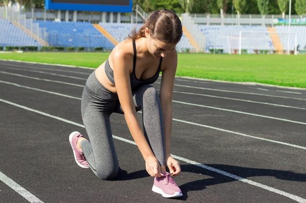 Die junge schöne sportläuferfrau, die ihre schuhspitzespitzee bindet, bereiten für das laufen vor, sport und eignungskonzept