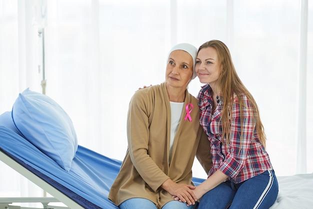 Die junge schöne tochter sitzt neben der mutter, die gegen den krebs kämpft, um sie im krankenhausbett zu unterstützen