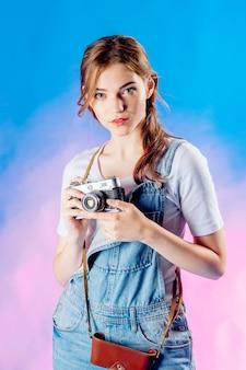 Die junge schönheit, die eine retro- kamera hält, wird reisen