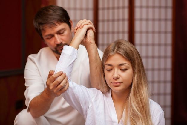 Die junge schönheit, die mit ihren augen lächelt, schloss während der thailändischen massagesitzung in der badekurortmitte. professioneller thailändischer masseur, der mit der kundin, ihren körper ausdehnend arbeitet. gesundheit, behandlung, genesung