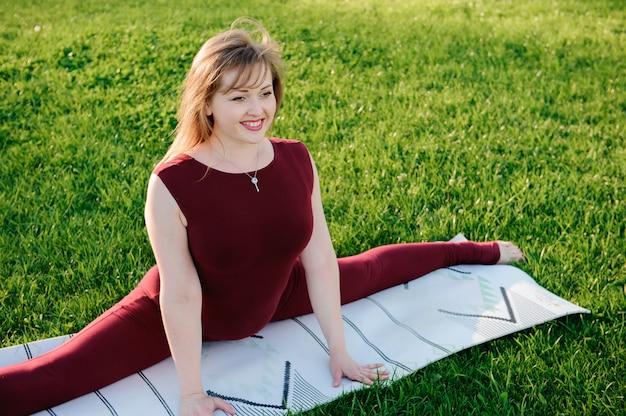 Die junge schönheit, die yoga tut, trainiert im park