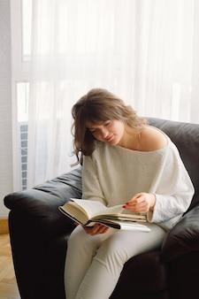 Die junge schönheitsfrau liest zu hause ein buch