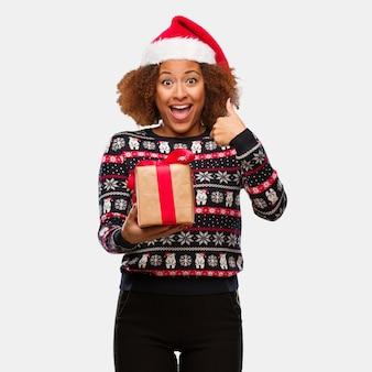 Die junge schwarze frau, die ein geschenk am weihnachtstag überrascht hält, fühlt sich erfolgreich und wohlhabend