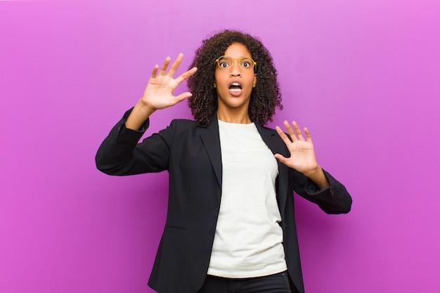 Die junge schwarze geschäftsfrau, die verblüfft und erschrocken sich fühlt und etwas fürchtet, das, wenn die hände offenes vorderes sprichwort sind, bleiben weg