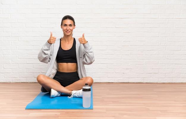 Die junge sportfrau, die auf dem boden mit dem mattengeben daumen sitzt, up geste