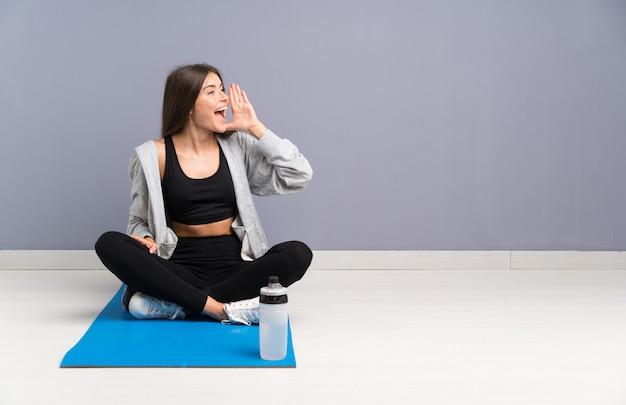 Die junge sportfrau, die auf dem boden mit der matte schreit mit dem breiten mund sitzt, öffnen sich
