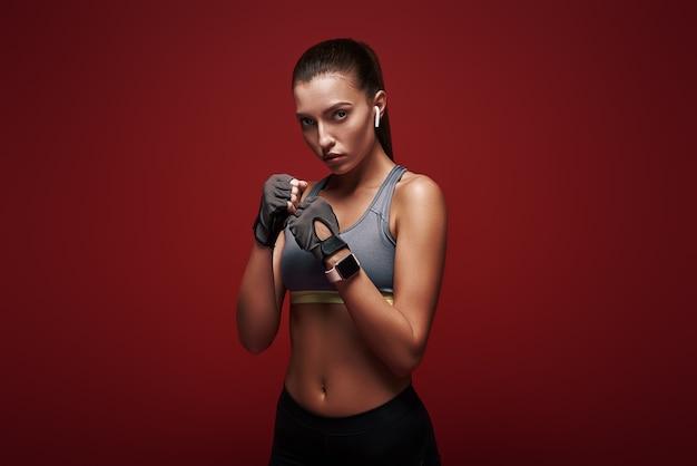 Die junge sportlerin des neuen meisters, die über rotem hintergrund steht, ist bereit, zu trainieren