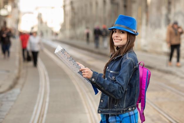 Die junge stilvolle frau, die auf die alte stadtstraße geht, reisen mit rucksack und blauem hut. ukraine, lemberg