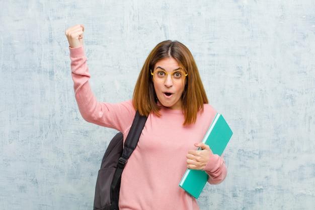 Die junge studentenfrau, die einen unglaublichen erfolg feiert, mögen einen sieger und schaut aufgeregt und das glückliche sprichwort nehmen das! gegen grunge