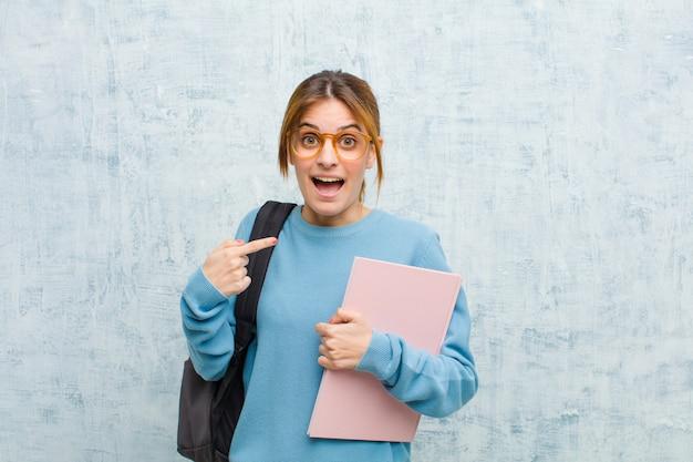 Die junge studentenfrau, die entsetzt und mit dem breiten mund überrascht schaut, öffnen sich und zeigen auf selbst
