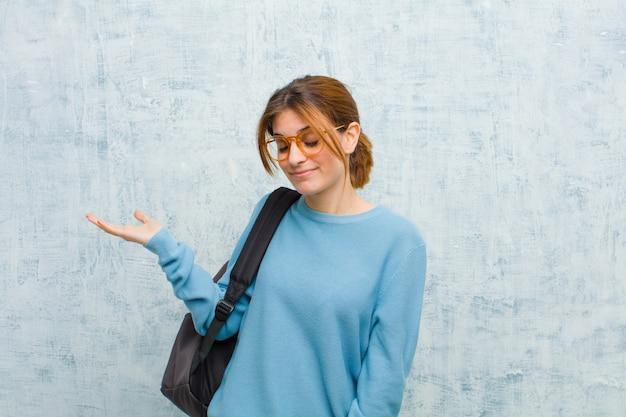 Die junge studentenfrau, die glücklich sich fühlt und zufällig lächelt, schauend zu einem gegenstand oder zu einem konzept, die auf der hand auf der seite gehalten werden