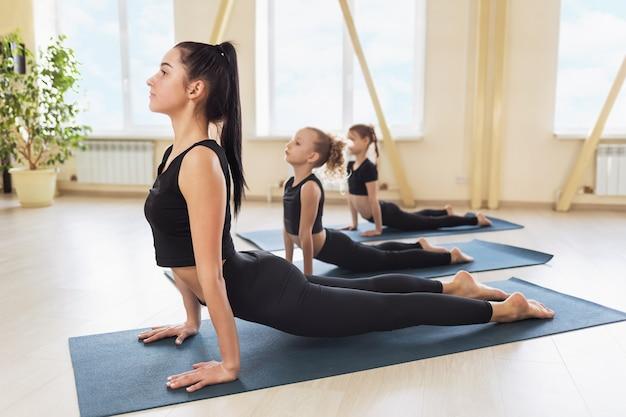 Die junge trainerin, die yoga praktiziert, zeigt ihren schülern, wie man die übung mit dem hund oder die urdhva mukha shvanasana-pose korrekt durchführt