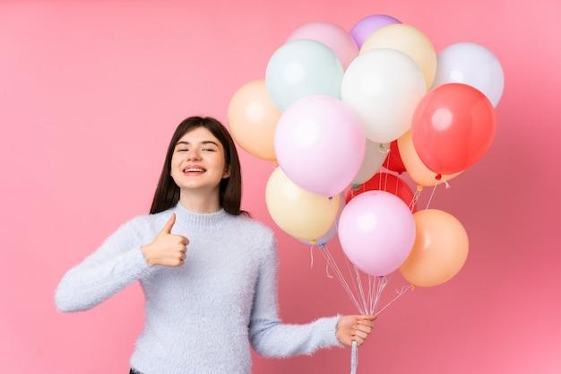 Die junge ukrainische jugendlichfrau, die viele ballone über dem lokalisierten rosa wandgeben daumen hält, up geste