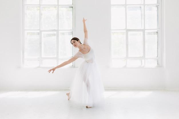 Die junge und unglaublich schöne ballerina posiert und tanzt in einem weißen studio