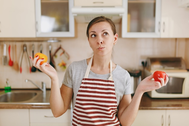 Die junge verwirrte und nachdenkliche frau in einer schürze entscheidet sich für eine rote oder gelbe tomate in der küche. diätkonzept. gesunder lebensstil. kochen zu hause. essen zubereiten.