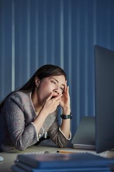 Die junge vietnamesische geschäftsfrau, die gähnt, wenn sie ein e-mail-dokument auf einem computermonitor liest, arbeitet in einem dunklen büro