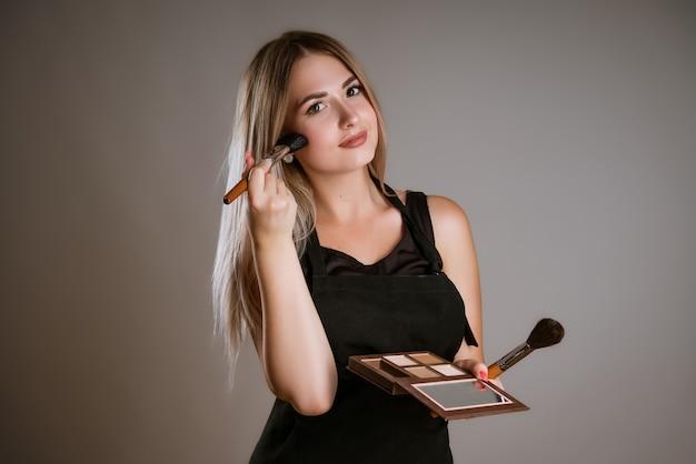 Die junge visagistin der blonden frau trägt kosmetik auf ein gepflegtes gesicht in einer dunkelheit auf