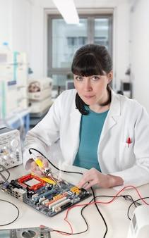 Die junge weibliche technologie, die eine leiterplatte lötet, betrachtet den zuschauer