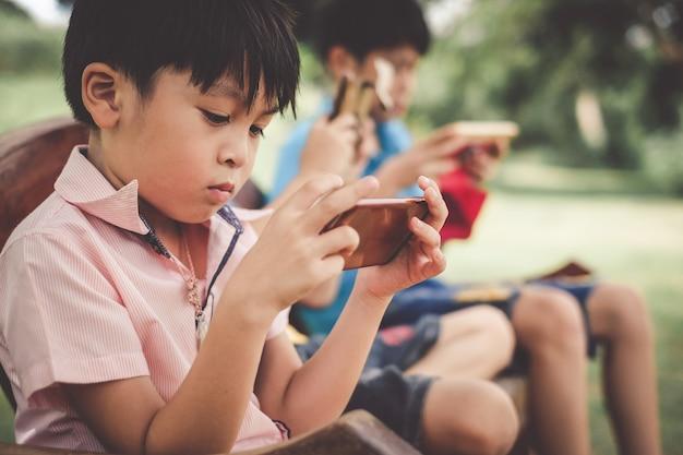 Die jungen achten darauf, tablet in der gruppe zu spielen. kinder, die süchtig nach spielen sind.