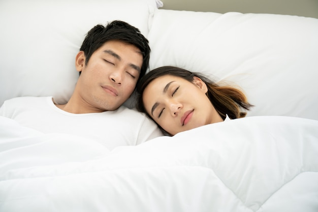 Die jungen asiatischen paare, die zusammen auf dem weißen bett schlafen, schließen oben.