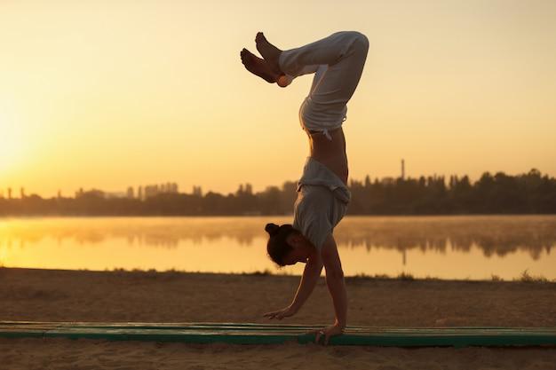 Die jungen athletischen männer, die im yoga stehen, werfen auf nahem see im park auf