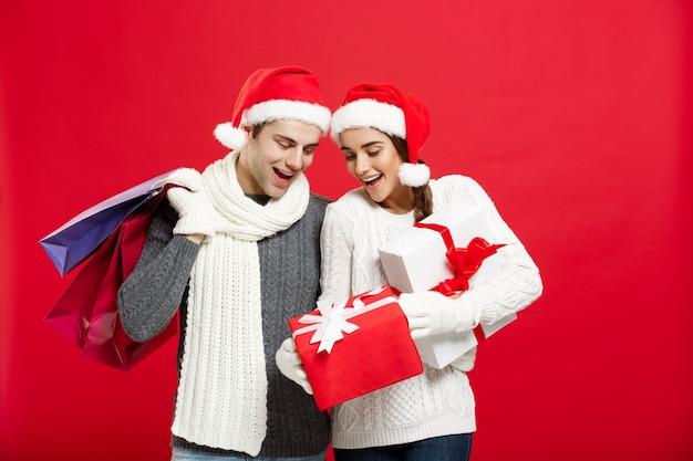 Die jungen attraktiven paare, die einkaufstasche halten, genießen, am weihnachtstag zu kaufen und zu feiern.