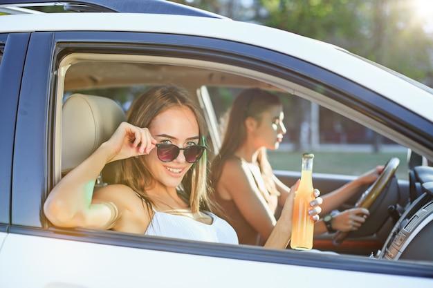 Die jungen frauen im auto lächeln